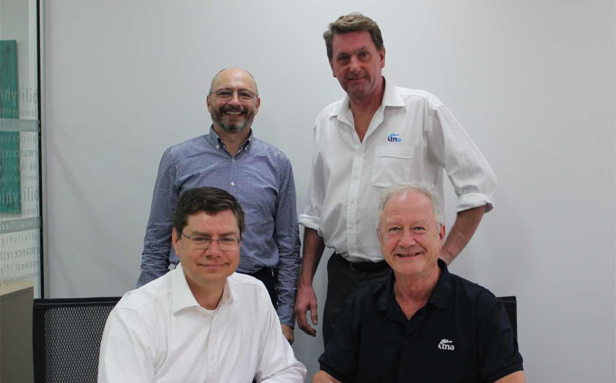 The deal was welcomed by executives of both companies, including CEOs Mark Mueller (front, left) and Alf Taylor (front, right).